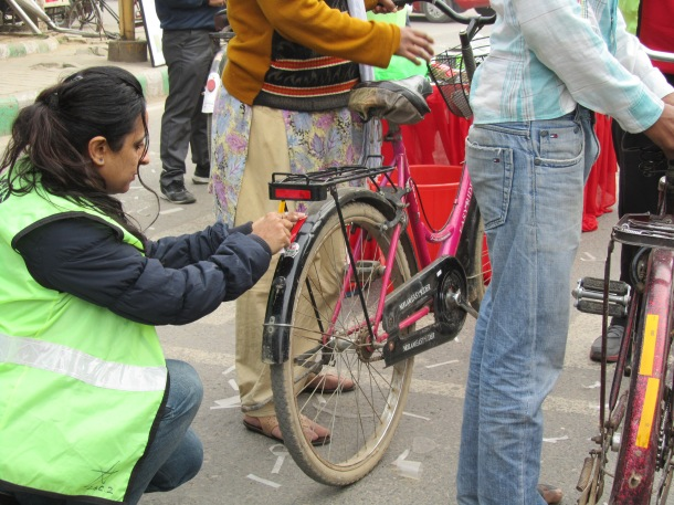 A volunteer fixes reflective tapes on a bicycle