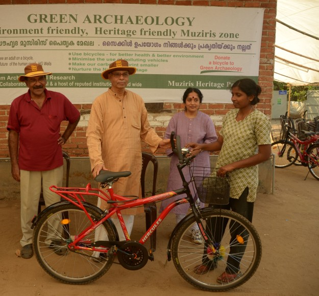 Kerala Council for Historical Research chairman Prof K N Panikkar (centre) and director Prof P J Cherian (left) launching the Green Archaeology project by handing over a cycle to an excavation employee